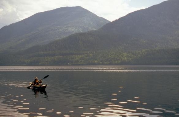 a sea kayaker paddles down a lake