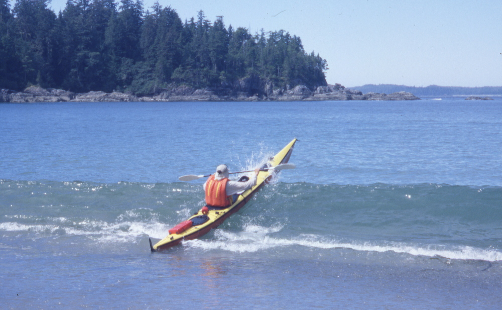 a sea kayak breaks out through surf